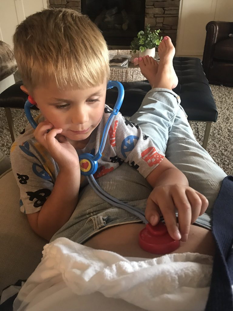 son listening to baby with toy stethoscope