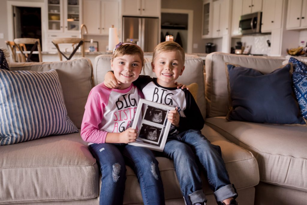 big brother and sister proudly holding ultrasound picture