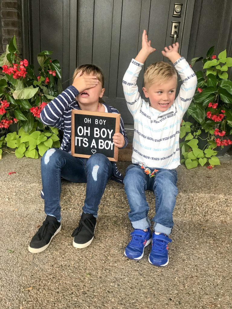 big kids sharing the baby gender reveal sign
